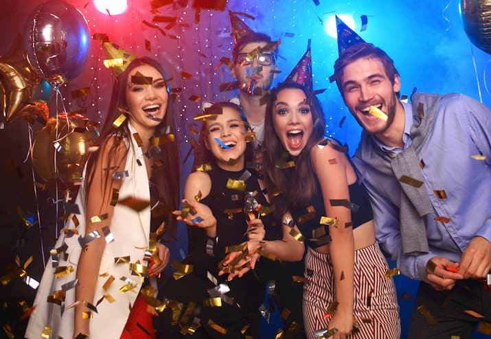 friends smile and throw confetti during a birthday celebration