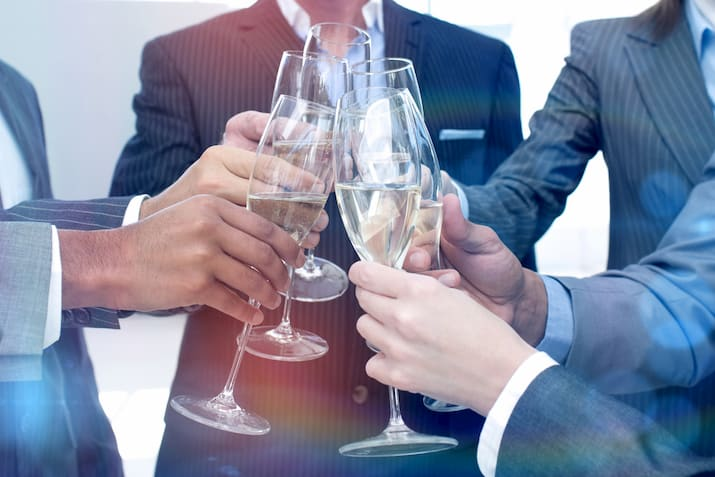 coworkers toast their champagne glasses in celebration of a business anniversary