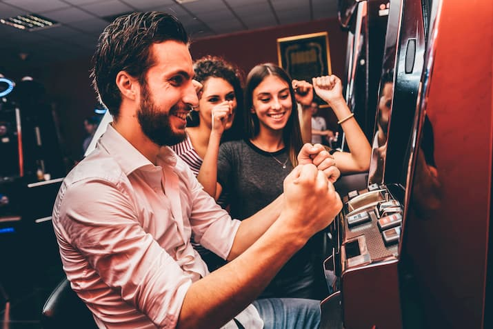 friends cheer at a casino slot machine