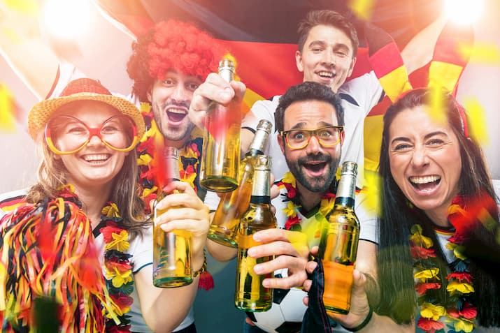 sports fans drink and cheer during a sporting event