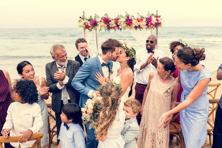 a bride and groom kiss with their friends and family surrounding them